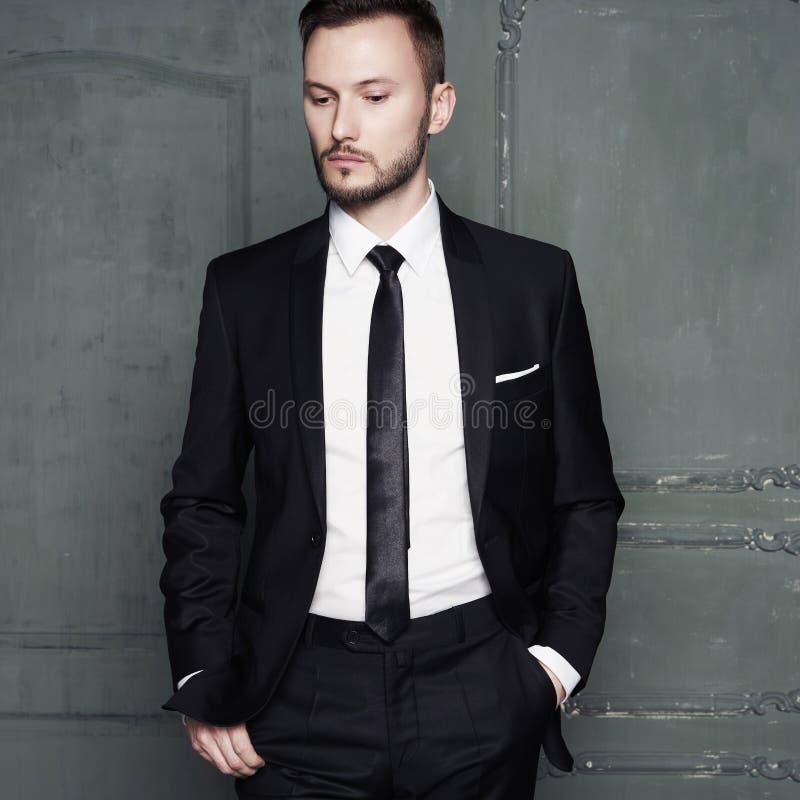 英俊的时髦的人画象典雅的黑衣服的 免版税库存照片