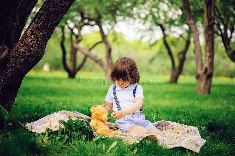 英俊的时髦的3岁小孩有滑稽的面孔的儿童男孩在悬挂装置享用在野餐的甜点 免版税库存图片