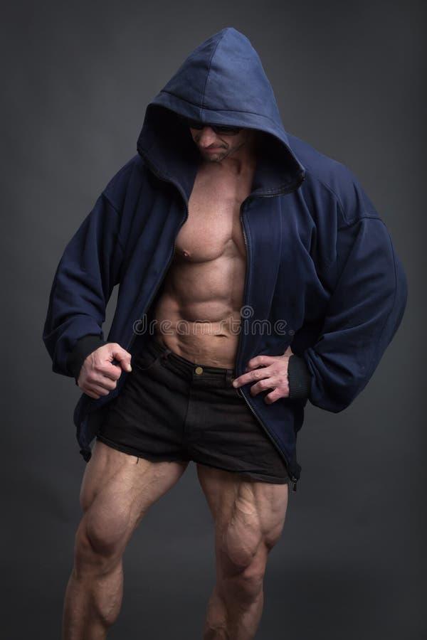 英俊的有伟大的体质的力量运动人在一蓝色有冠乌鸦 库存照片