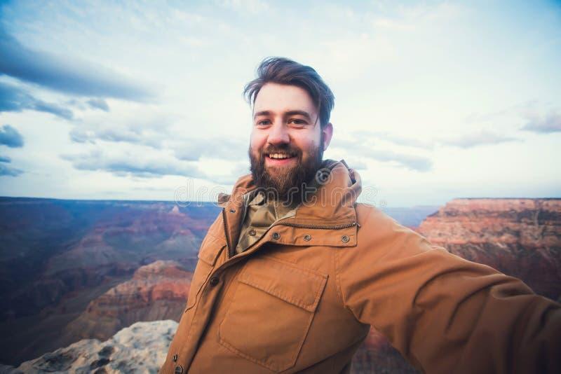 英俊的有胡子的人在远足在大峡谷的旅行做selfie照片在亚利桑那 免版税库存图片