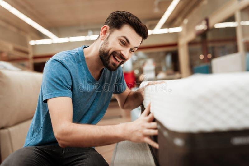 英俊的有胡子的人测试在家具店的床垫 一个健康姿势的矫形床垫 免版税库存图片