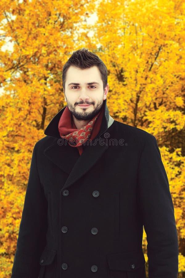 英俊的有胡子的人画象在秋天的穿黑外套 免版税库存图片