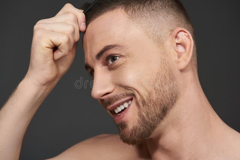 英俊的有胡子的年轻人身分画象反对灰色背景的 免版税库存照片