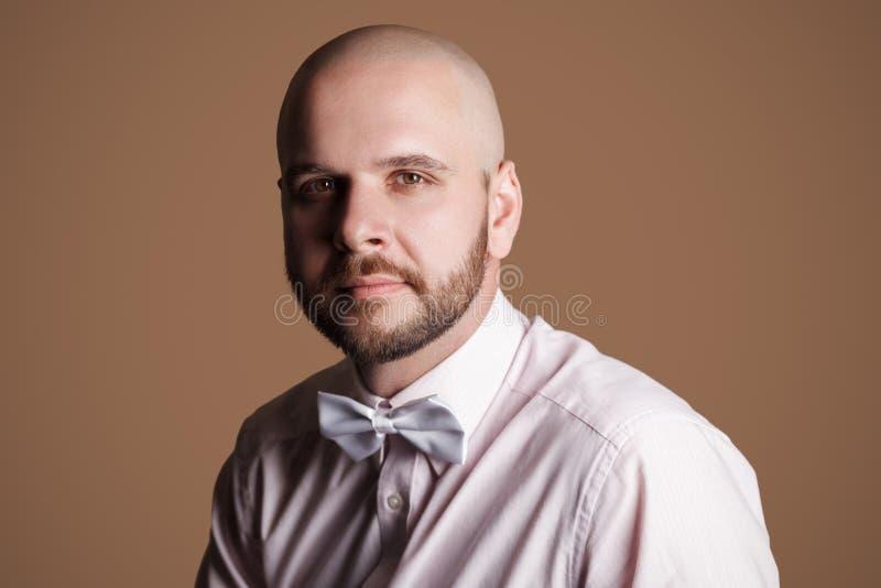 英俊的有胡子的秃头人特写镜头画象浅粉红色的shir的 库存照片