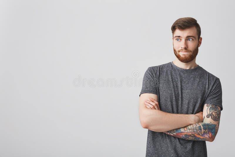 英俊的有胡子的行家人画象有黑发的和纹身花刺给看装袖子在旁边用横渡的手和玩事不恭 库存照片