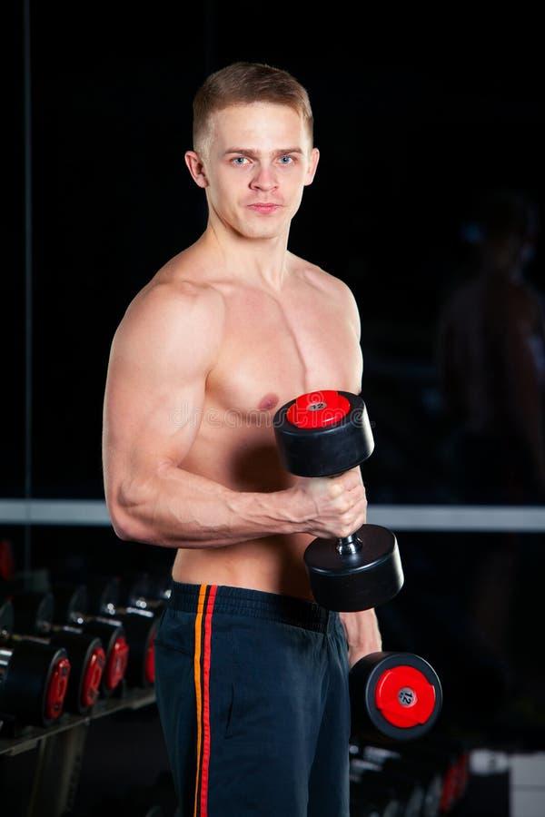 英俊的有今后确信地看的哑铃的力量运动人 坚强的爱好健美者六块肌肉,完善的吸收 免版税库存图片