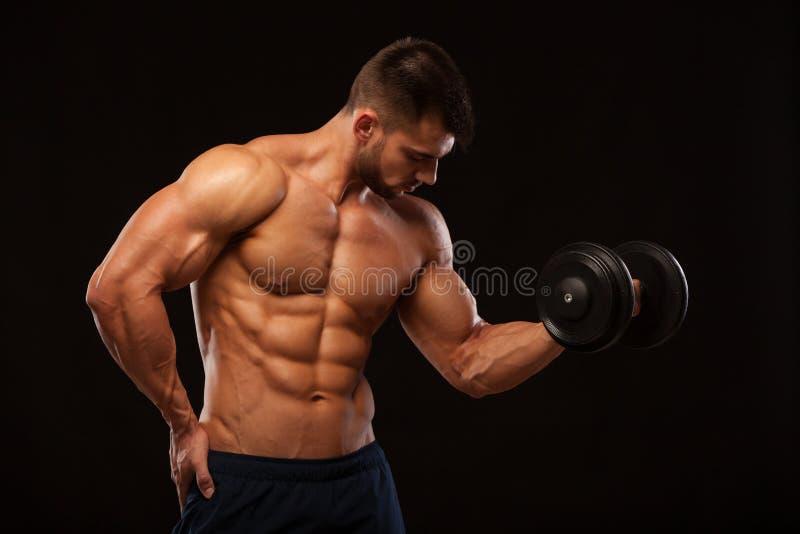 英俊的有今后确信地看的哑铃的力量运动人 有六块肌肉的,完善的吸收坚强的爱好健美者 库存图片