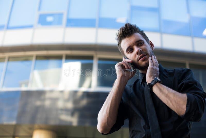 英俊的残酷在礼服或企业家打扮的人熟练的办公室工作者谈话通过手机在工休期间 库存图片