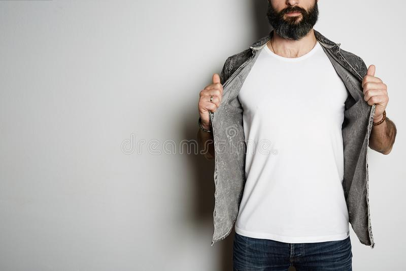 英俊的残酷有胡子的行家模型在黑牛仔裤衬衣和空白白色T恤优质夏天棉花摆在,在白色 免版税库存图片
