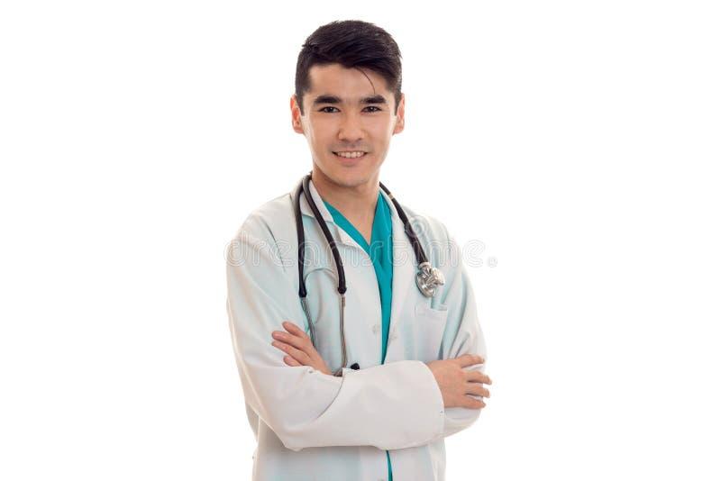 年轻英俊的深色的人医生画象白色制服的有看照相机和微笑的听诊器的 免版税库存照片