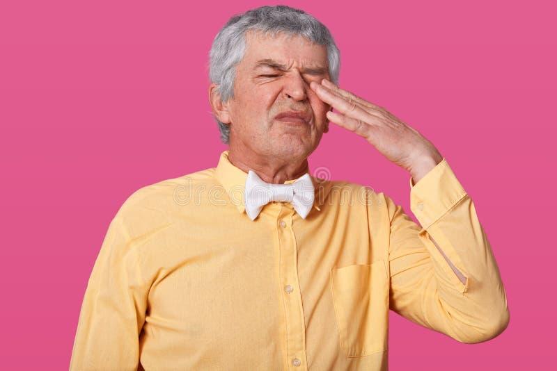 英俊的灰发的成熟人接近的画象保留在他的眼睛的手指,并且摩擦它,穿在一口气的黄色衬衣和 库存图片