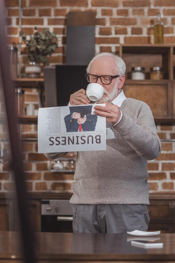 英俊的灰色头发人饮用的咖啡和读商业报纸 图库摄影