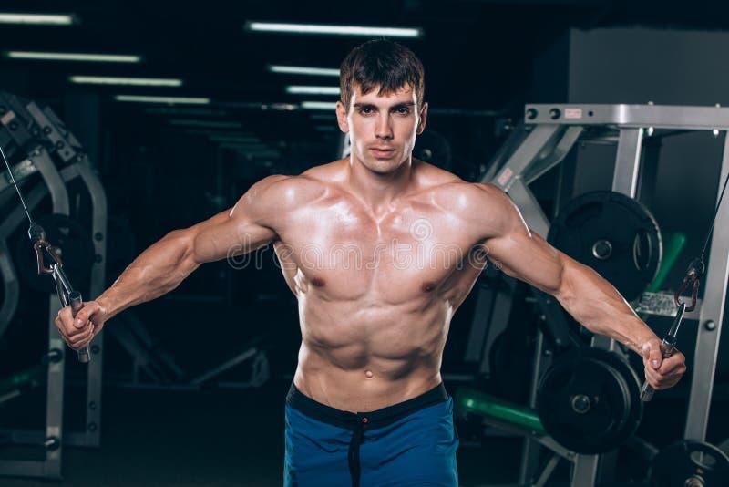 英俊的爱好健美者制定出增加在健身房的锻炼 免版税图库摄影