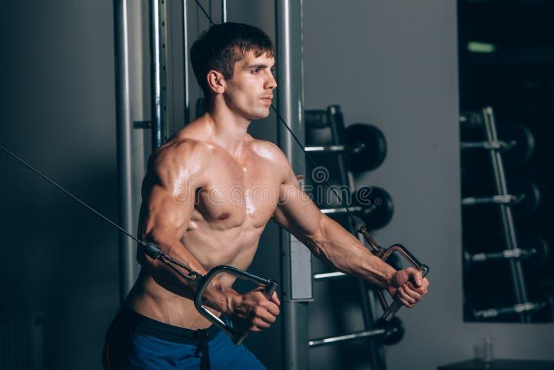英俊的爱好健美者制定出增加在健身房的锻炼 免版税库存图片