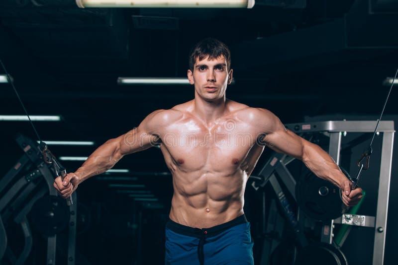 英俊的爱好健美者制定出增加在健身房的锻炼 库存照片
