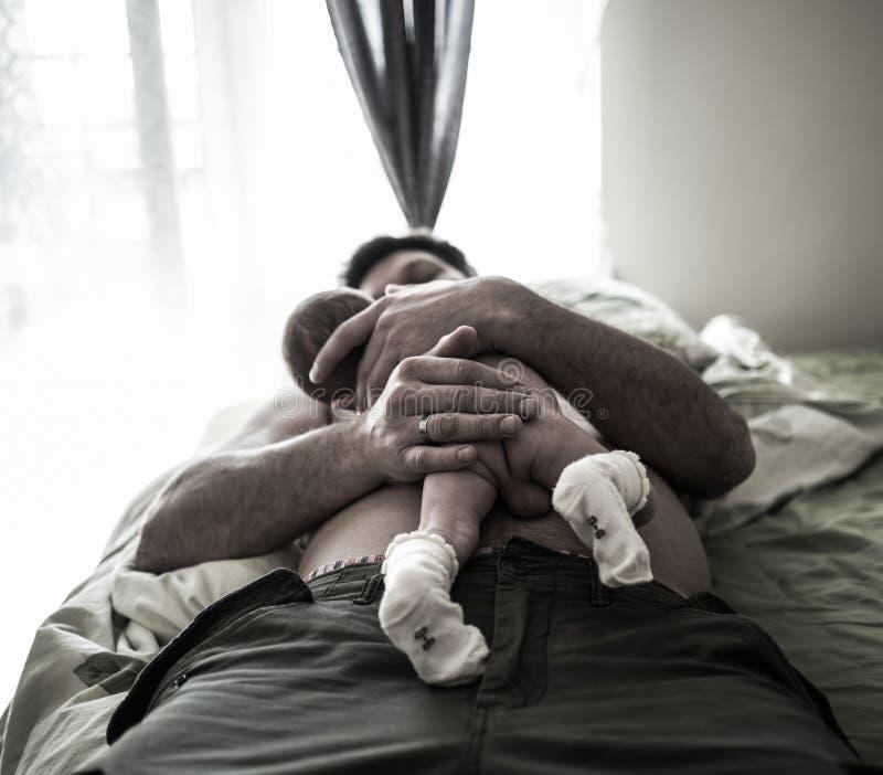 英俊的父亲在床上说谎并且小心拿着他的甜新出生的小儿子 免版税图库摄影