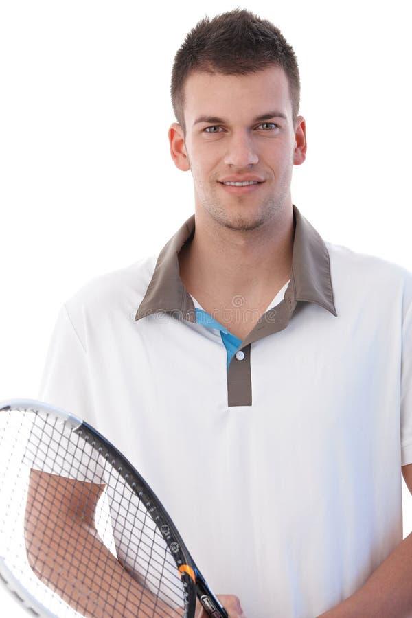 英俊的球员纵向微笑的网球 免版税库存图片