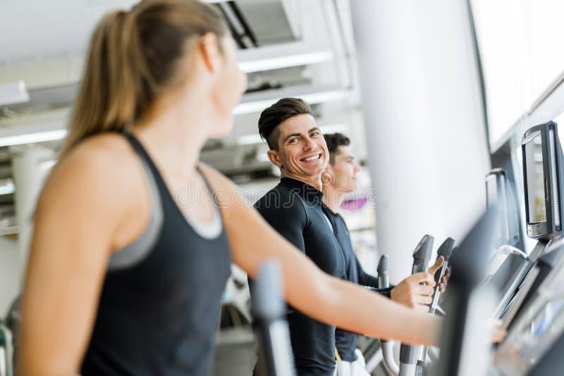 英俊的男人和使用步进的美丽的少妇在健身房 免版税库存图片