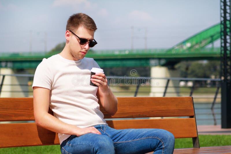 英俊的男孩佩带的太阳镜,坐在码头和饮用的咖啡的一条长凳去 从城市仓促的休假 免版税图库摄影