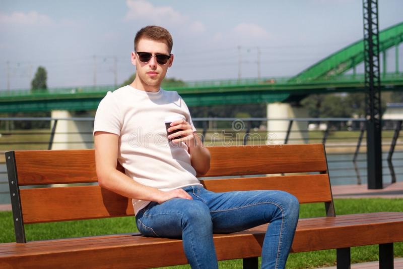 英俊的男孩佩带的太阳镜,坐在码头和饮用的咖啡的一条长凳去 从城市仓促的休假 免版税库存照片