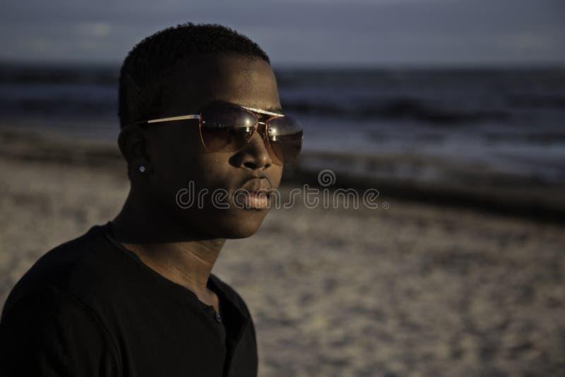 英俊的男孩坐海滩 图库摄影