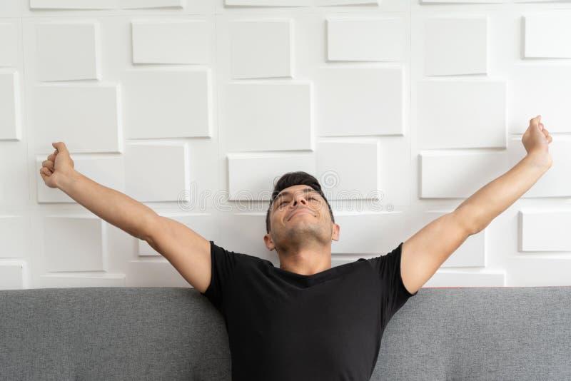 英俊的男性在睡眠以后伸手在早晨 库存图片