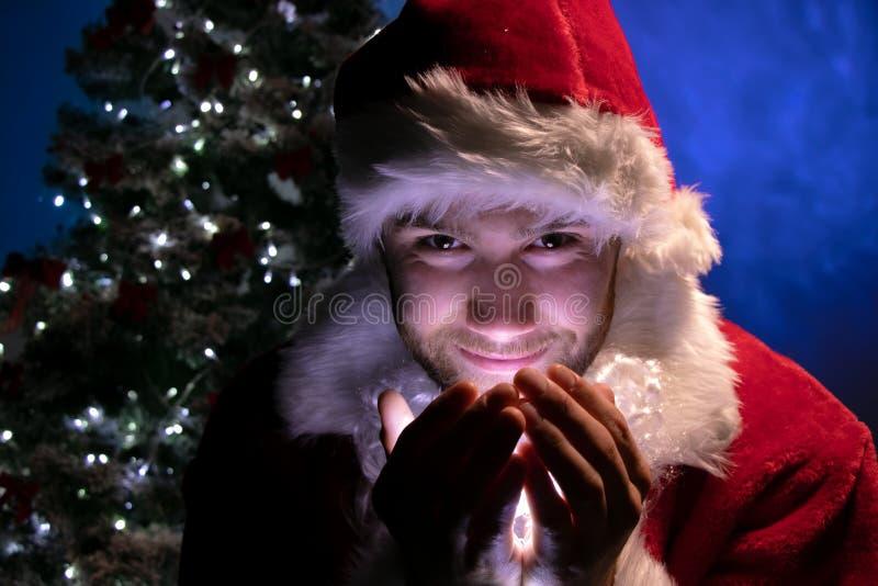 英俊的男性微笑和在他的手上拿着光和看与圣诞树的圣诞老人照相机在背景中 库存照片