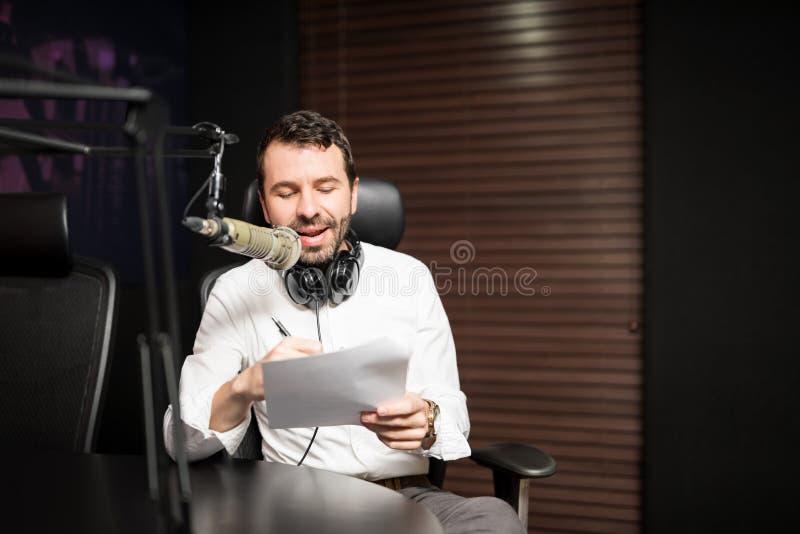 英俊的男性无线电主人在演播室 免版税库存图片