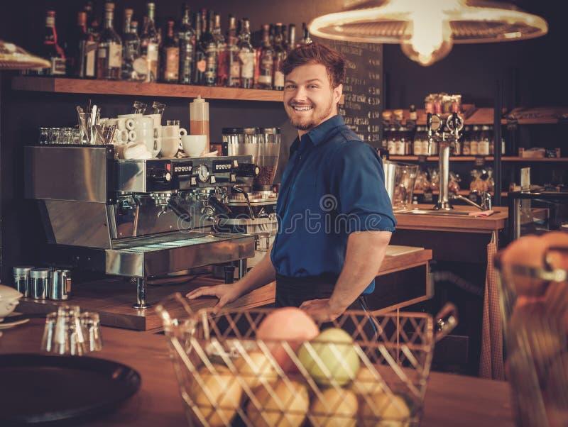 英俊的男服务员获得乐趣在酒吧柜台在面包店 库存图片