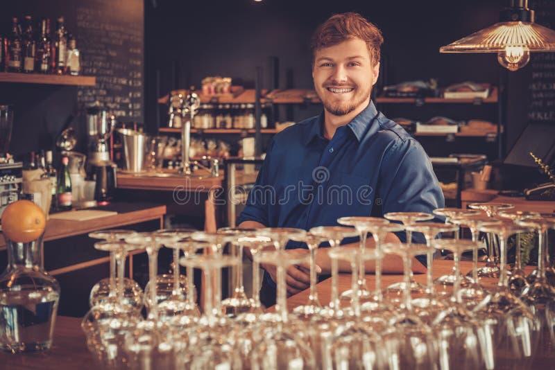英俊的男服务员获得乐趣在酒吧柜台在面包店 免版税库存图片