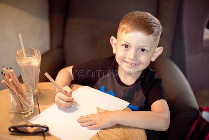 英俊的白种人小男孩绘画在桌上 库存图片