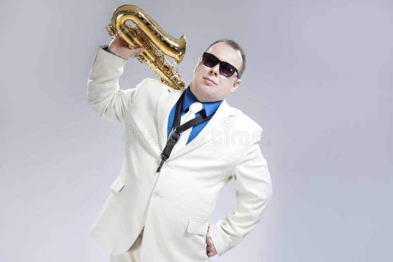 英俊的白种人萨克管演奏员画象有乐器的在肩膀 库存照片