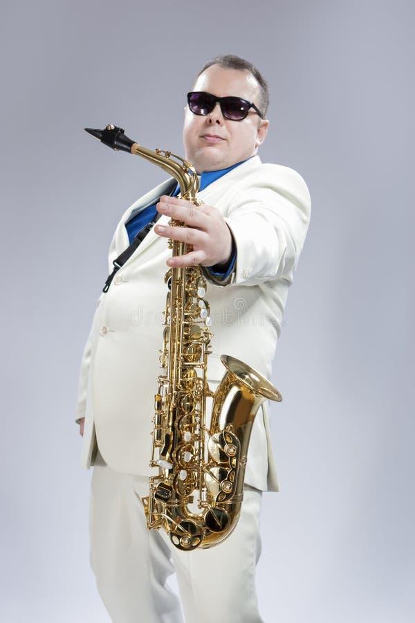 英俊的白种人萨克管演奏员画象有音乐的Instr 免版税库存照片