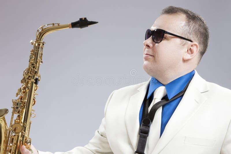 英俊的白种人萨克管演奏员画象有音乐的Instr 库存照片