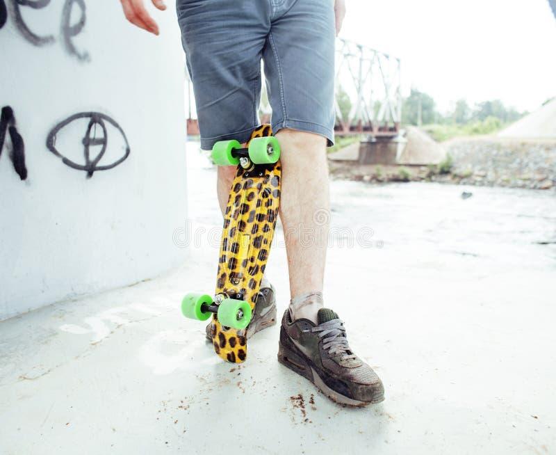 年轻英俊的真正的hipsrter人有胡子停留在与豹子滑板,生活方式人的桥梁extreeme下 库存图片