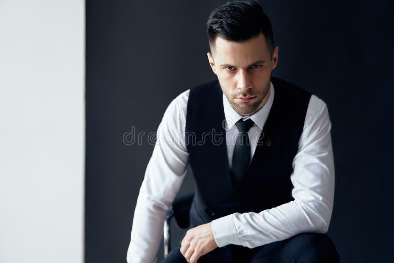 英俊的确信的人画象坐椅子和摆在 免版税库存图片