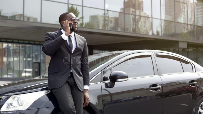英俊的美国黑人的人谈话在有微笑的电话在面孔在办公室附近 免版税库存照片