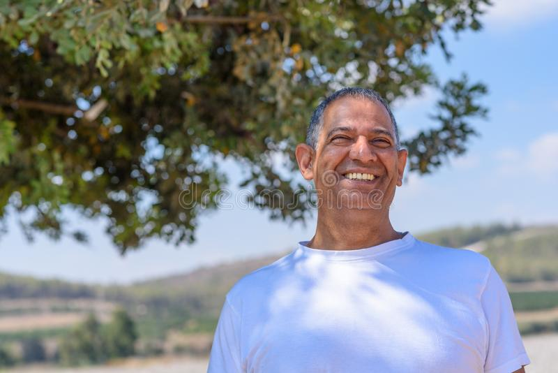 英俊的老活跃老人户外画象  与亲切的眼睛和美好的微笑的成熟男性 免版税库存照片