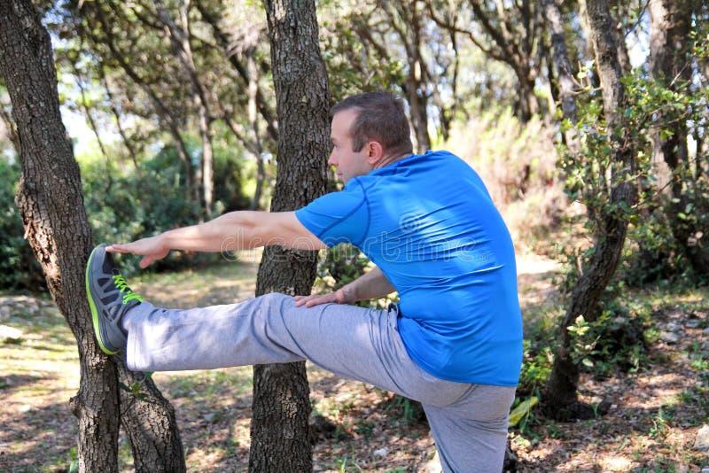 英俊的肌肉年轻人做着舒展在森林运动员佩带的运动服的锻炼在室外风景的自然 免版税库存照片
