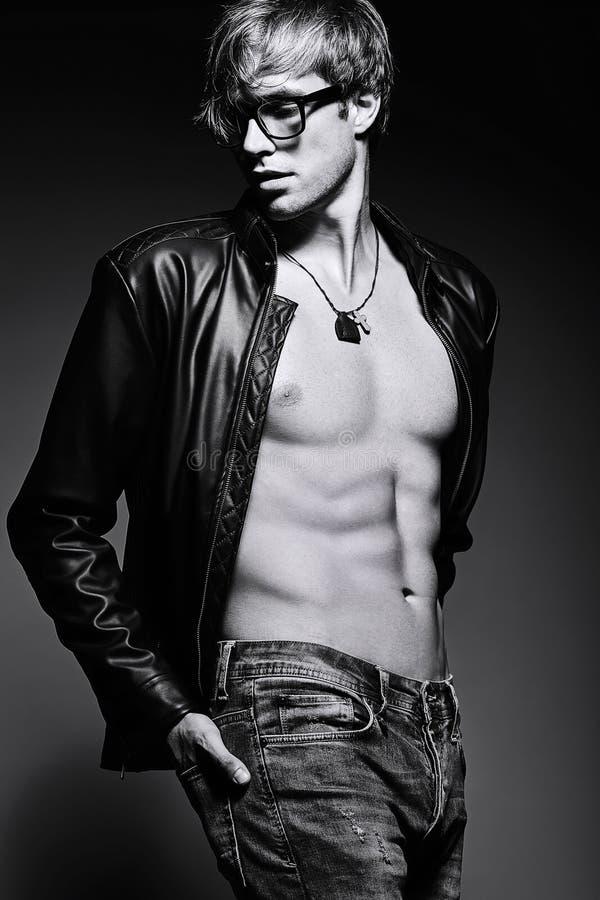 英俊的肌肉的摆在演播室的适合男性式样人显示他的腹肌 免版税库存图片