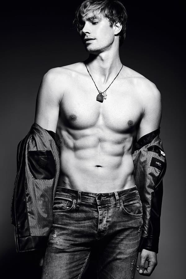 英俊的肌肉的摆在演播室的适合男性式样人显示他的腹肌 库存图片