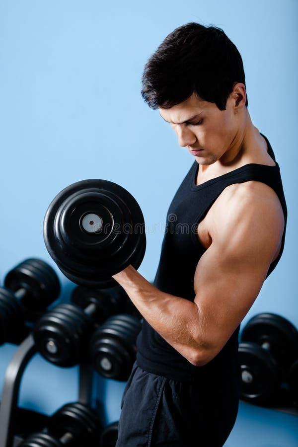 英俊的肌肉运动员使用他的哑铃 免版税库存图片