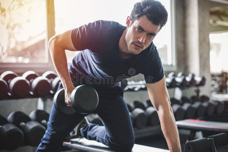 英俊的解决与在健身房的哑铃的举重运动员举的卧推 库存照片