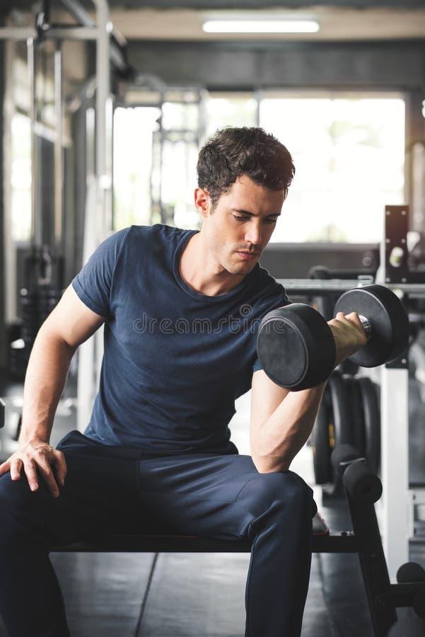 英俊的解决与在健身房的哑铃的举重运动员举的卧推 库存图片