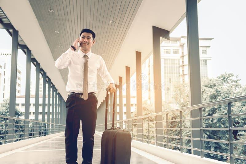 英俊的谈话在机动性和举行suitca的企业亚裔人 库存照片