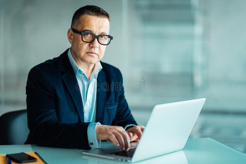 英俊的资深商人画象使用膝上型计算机的,当看照相机时 免版税库存照片