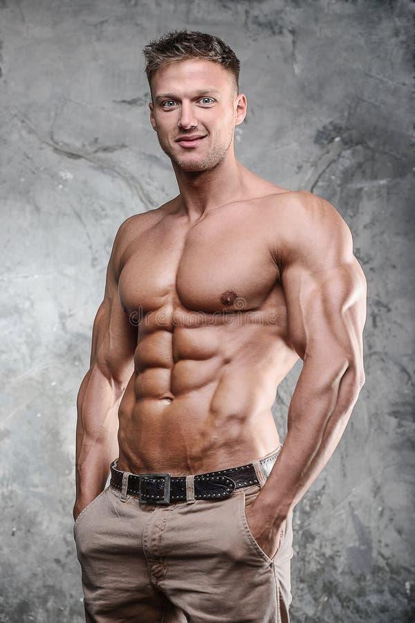 英俊的运动摆在一灰色backgrou的健身肌肉人 免版税库存图片