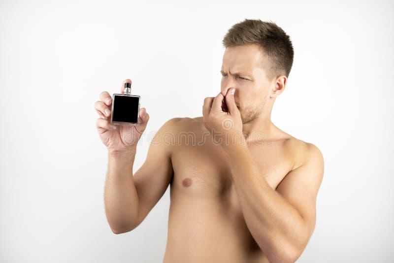 英俊的适合的人的图象有拿着parfume和关闭他的鼻子用另一只手的赤裸躯干的在一只手上白色 免版税库存图片