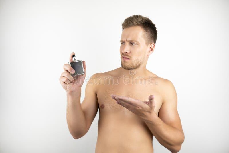 英俊的适合的人的图象有拿着parfume和指向白色被隔绝的背景的赤裸躯干的在一只手上 图库摄影