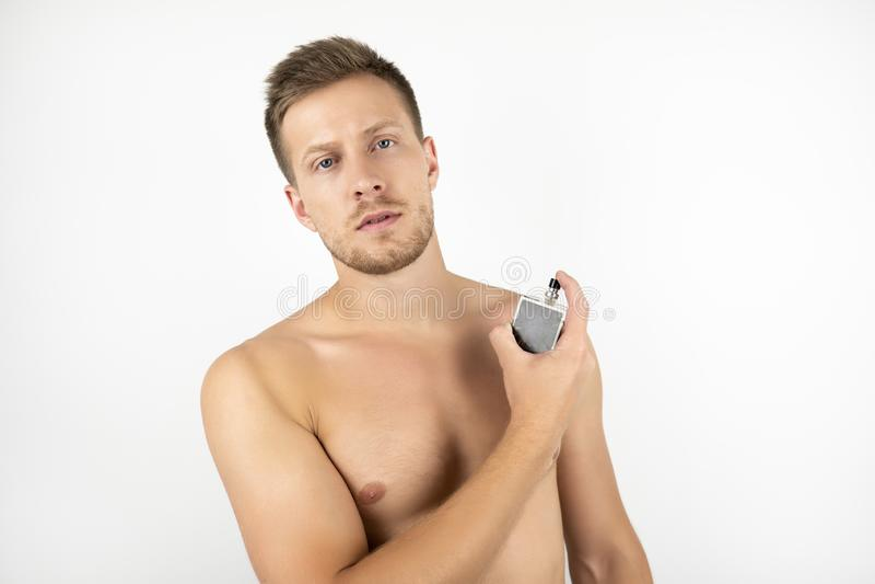 英俊的适合的人的图象有拿着parfume白色被隔绝的背景的赤裸躯干的 库存图片